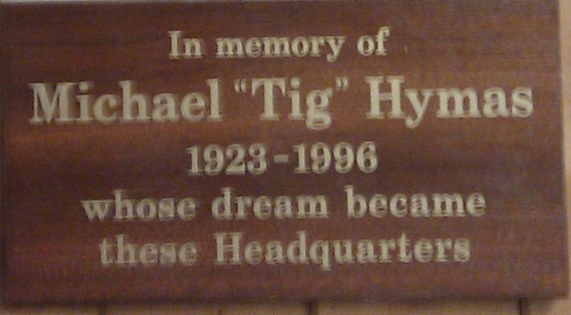 Wooden memorial plaque stating: In memory of Michael 	   'Tig' Hymas 1923-1996 whose dream became these 	   Headquarters.